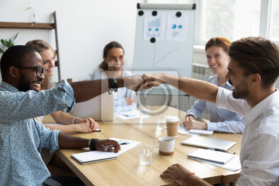 Obraz Diverse company staff girls guys sitting at desk in boardroom feel happy and satisfied celebrating success at work. Diverse colleagues fist bumping greeting each other express friendship and respect