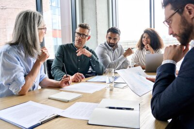 Obraz Diverse international executive business partners group discuss report at boardroom meeting table. Multiracial team negotiating project developing business strategy doing paperwork analysis in office.