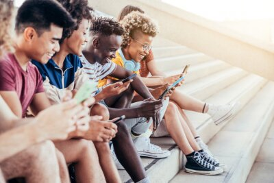 Obraz Diverse teenage students using digital smart mobile phones on college campus - Group of friends watching cellphones sharing content on social media platform - Youth, friendship and technology concept