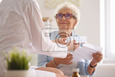 Obraz Doctor giving medicine and instruction to senior woman at home