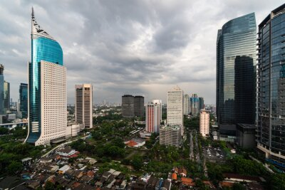 Dramatic sky over Jakarta downtown skyline where modern skyscrapers contrasts with poor residential district in Indonesia capital city
