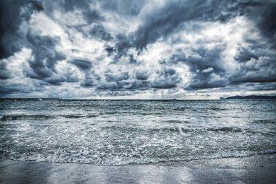Obraz dramatyczne pochmurne niebo nad brzegiem