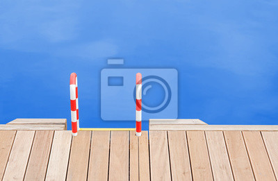 Drewniane molo i drabiny przez niebieski wody.