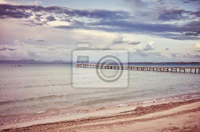Drewniany molo na plaży przy wschodem słońca, barwi stonowanego obrazek, Mallorca, Hiszpania.