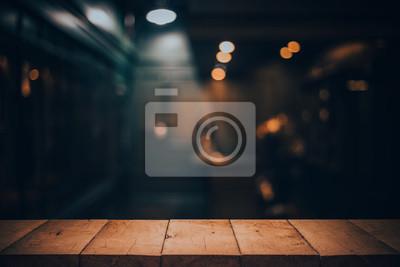 Obraz Drewniany stołowy wierzchołek na zamazanym kontuar kawiarni sklep z żarówką. Tło dla montażu produktu pokazu lub projekta klucza projekta