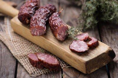 Obraz Dried sausage on kitchen plank