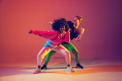 Obraz Drive in motion. Stylish man and woman dancing hip-hop in bright clothes on green background at dance hall in neon light. Youth culture, movement, style and fashion, action. Fashionable portrait.