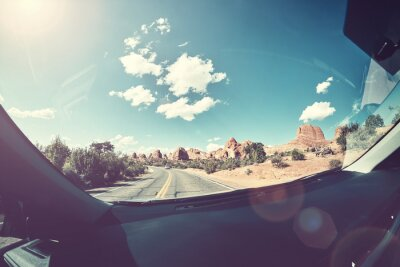 Driving against the sun, vintage toned picture of a road taken from front seat of a car, lens flare present, USA.