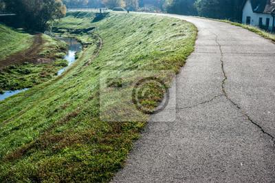 Droga z szarego kamienia z pęknięć na wysokim obszarze zielonej trawie z małego potoku w marży, w Szentendre w mieście, Budapeszcie