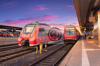 Duża prędkość czerwony pociągów podmiejskich na stacji kolejowej i kolorowe niebo o zachodzie słońca w Europie. Krajobraz przemysłowy z piękną platformą kolejową i nowoczesne pociągi latem. Popędzać.