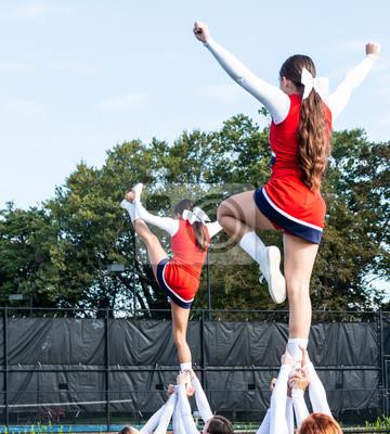 Obraz Dwa licealne cheerleaderki trzymane za kostki