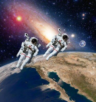 Obraz Dwóch astronautów Spaceman planeta Ziemia w przestrzeni kosmicznej księżyca Droga Mleczna. Elementy tego zdjęcia dostarczone przez NASA.