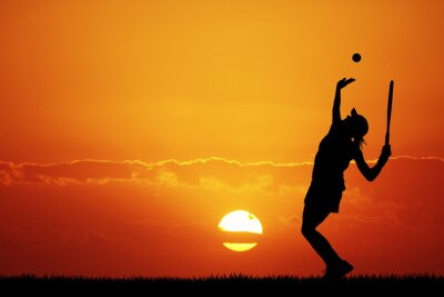 Obraz Dziewczyna gra w tenisa na zachodzie słońca