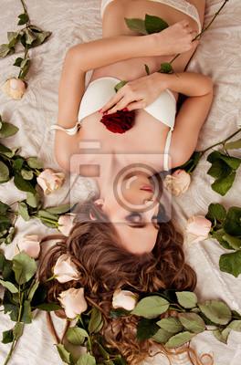 Obraz dziewczyna, która leży w bieliźnie na łóżku z róż