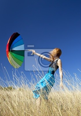 Dziewczyna Redhead z parasolem w wietrzny łąkowej.