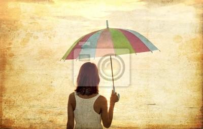 Dziewczyna z parasolem na brzegu morza. Zdjęcie w starym stylu obrazu.