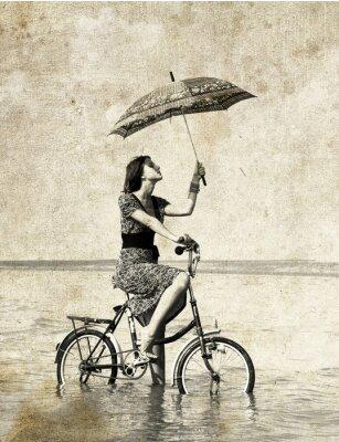 Dziewczyna z parasolem na rowerze. Zdjęcie w starym stylu obrazu .