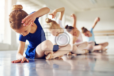 Obraz Dziewczynki zginania siedzi na podłodze w klasie baletu