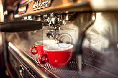 Obraz ekspres do kawy przygotowuje świeżą kawę i wlewając do czerwonych kubków w restauracji, barze lub pubie.