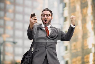 Obraz Ekstatyczny zadowolony biznesmen sprzedaży wykonawcze gesty radości podekscytowany z okazji po dobrych wiadomości