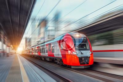 Obraz Electric passenger train drives at high speed among urban landscape.