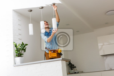 Obraz Electrician is installing and connecting a lamp to a ceiling.