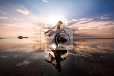 Obraz Elegancka kobieta tańczy na wodzie. Zachód słońca i sylwetka.