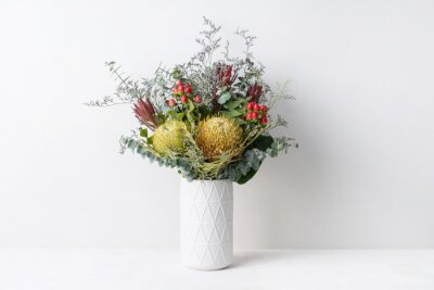 Obraz Elegant flower arrangement of a dried Banksia surrounded by misty blue, red leucadendrons and Australian eucalyptus, in a white vase on a table. Could be a gift on display or decoration.