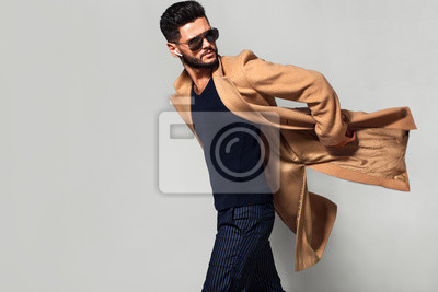 Obraz Elegant young handsome main coat wearing glasses. Studio fashion portrait.