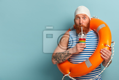 Obraz Embarrassed holiday maker drinks cold summer cocktail, spends free time at beach, wears swimcap sailor t shirt, swims with lifebuoy, has surprised expression, models over blue wall with free space