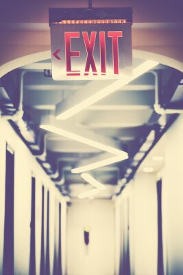 Emergency exit sign in empty corridor, selective focus, color toning applied.
