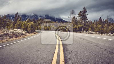 Empty mountain road in Grand Teton National Park, focus on asphalt, color toned picture, Wyoming, USA.