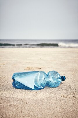 Empty plastic bottle on a beach, selective focus, color toning applied.