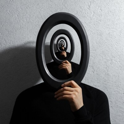 Obraz Enigmatic surrealistic optical illusion, young man holding round frame on textured grey background.