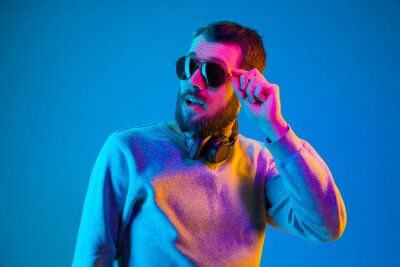 Obraz Enjoying his favorite music. Happy young stylish man in hat and sunglasses with headphones listening and smiling while standing against blue neon background