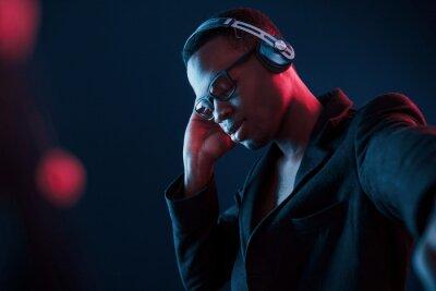Obraz Enjoying listening music in headphones. In glasses. Futuristic neon lighting. Young african american man in the studio