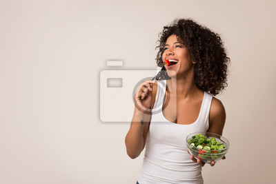 Obraz Excited lady eating healthy salad over light background