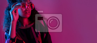 Obraz Fashion young african girl black woman wear stylish pink sunglasses glasses looking at camera isolated on party purple studio background, horizontal banner for website design, portrait, copy space