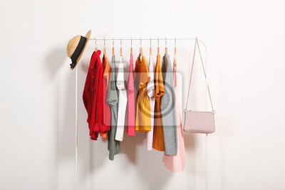 Obraz Fashionable clothes on hangers on a wardrobe rack on a light background.