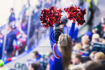 Obraz Female cheerleader in red blue uniform with pom-pom with audience in the background performing and supporting during ice hockey game match