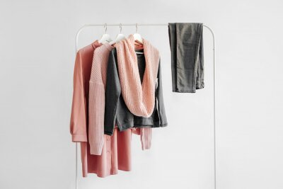 Obraz Female clothes in pastel pink and gray color on hanger on white background.  Jumper, shirt, jeans and scarf. Spring/autumn outfit. Minimal concept.