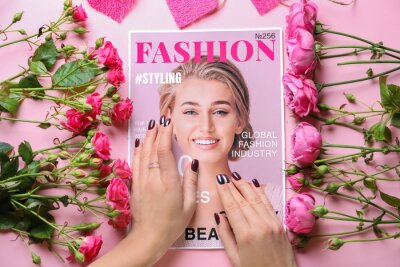 Obraz Female hands with fashionable magazine and flowers on color background