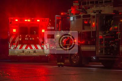 Obraz fire truck, firefighter, ambulance responding to car crash at night