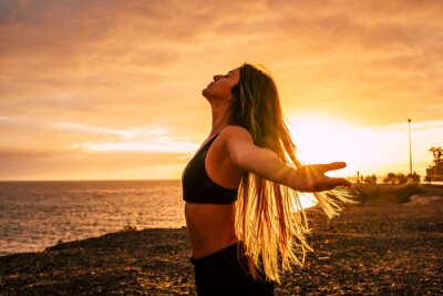 Obraz Fitness happy and free young woman enjoy the sunset after the sport workout activity session taking breathe - body health care people concept with beautiful woman outdoor opening arms