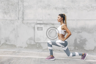 Obraz Fitness sport woman in fashion sportswear doing workout over gray wall
