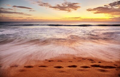 Footprints on a tropical beach at sunset, long exposure picture.
