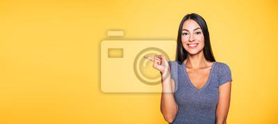 Obraz Fotografia młoda z podnieceniem piękna szczęśliwa brunetki kobieta, dziewczyna wskazuje daleko od i uśmiech odizolowywający na żółtym tło sztandarze