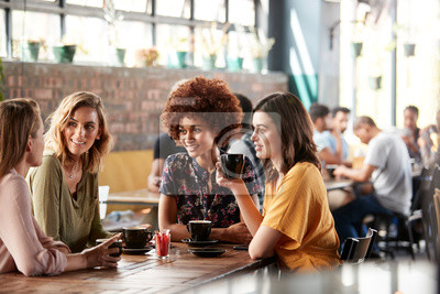 Obraz Four Young Female Friends Meeting Sit At Table In Coffee Shop And Talk