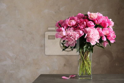 Obraz Fragrant peonies in vase on table against color background, space for text. Beautiful spring flowers