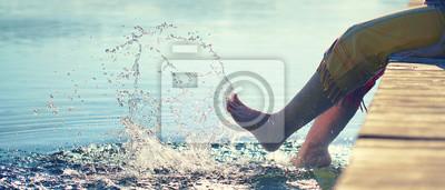 Obraz Frau plantscht mit den Füßen im See